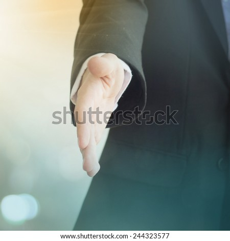 A young business man ready to shake hands - stock photo