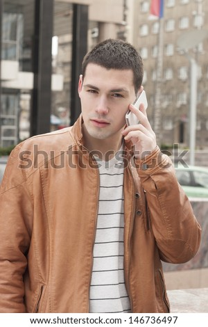 A young business man with a smart phone, standing in front of an office building. - stock photo
