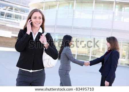 A  young business woman on the phone with coworkers shaking hands at office building - stock photo