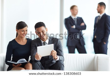 A young businessman and his colleague discussing data in notepad in working environment - stock photo
