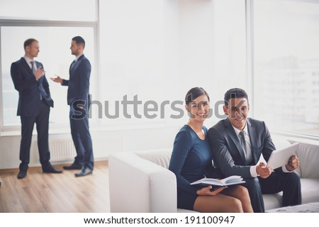 A young businessman and his colleague looking at camera while working in office - stock photo