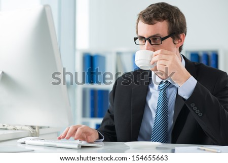 A young businessman drinking a morning coffee at his workplace and typing on the foreground - stock photo