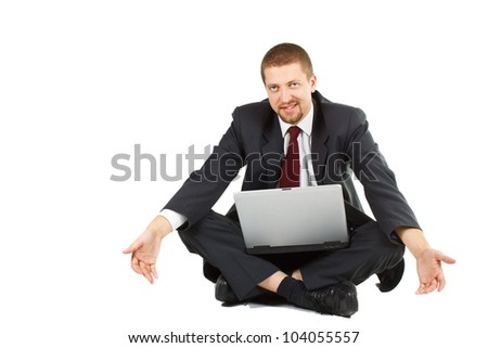A young businessman in suit and tie sitting crossed legs, laptop in his lap, looking helpless with an uncomfortable smile, spreading arms helplessly - isolated on white - stock photo