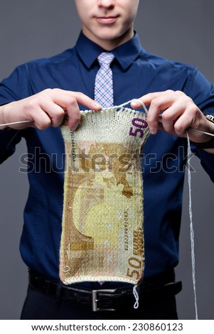 A young businessman is knitting thing, which look like as euro banknote. - stock photo