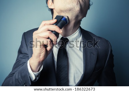 A young businessman is shaving with an electric razor - stock photo