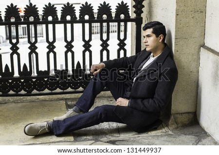 A young businessman is sitting on the ground and take a break. - stock photo