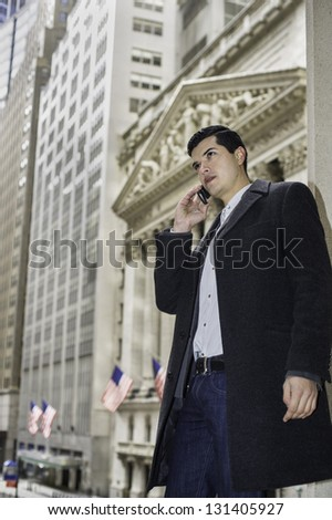 A young businessman is standing outside of a business district and talking on the phone/Business Man Talking on the Phone - stock photo
