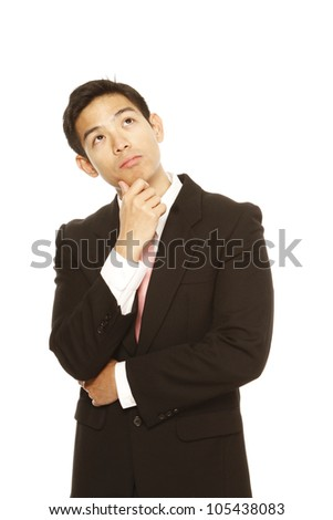 A young businessman looking up and thinking - stock photo
