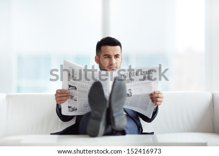A young businessman on sofa reading newspaper in the office - stock photo