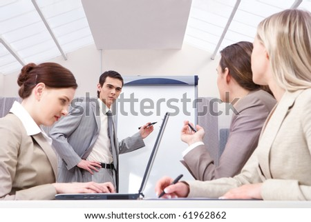 A young businessman representing a project, his three colleagues sitting at table and looking at him - stock photo
