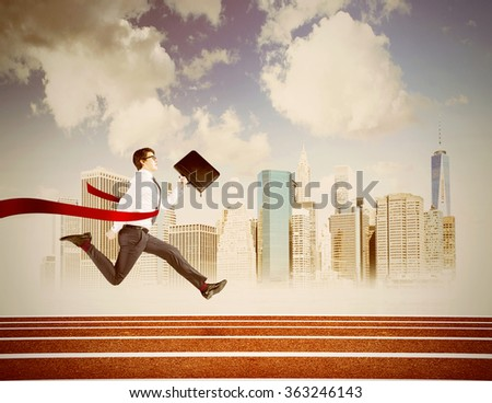 A young businessman running forward on track with a black folder in hand crossing the red finish line. New York at the background. Filter. Concept of victory. - stock photo