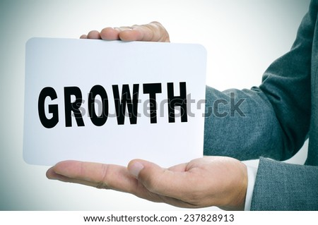 a young businessman showing a signboard with the text growth written in it - stock photo