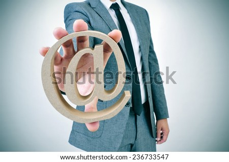 a young businessman showing an at sign in his hand - stock photo