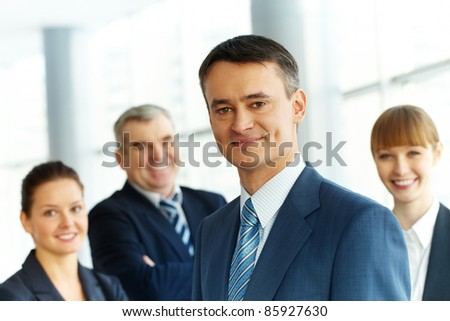 A young businessman smiling against three partners - stock photo