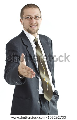 A young businessman wearing glasses, suit and tie is giving a hand ready to shake hands,left hand is in pocket - isolated on white - stock photo