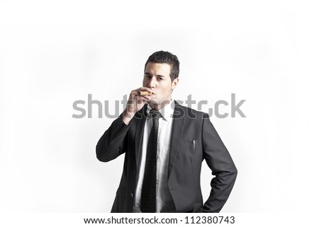 A young businessman with a tie smokes a cigar - stock photo