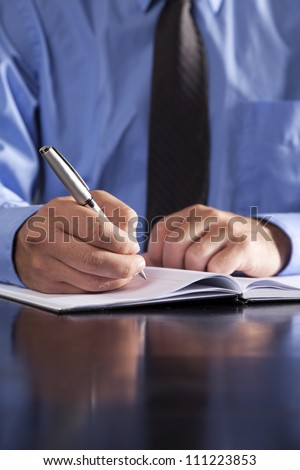 A young businessman writes in a notebook while sitting at a desk. - stock photo