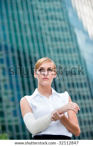 A young businesswoman holds her injured arm against city backdrop - stock photo