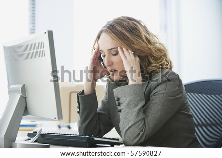 A young businesswoman is looking stressed as she works at her computer. Horizontal shot. - stock photo