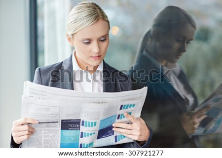 A young businesswoman reading the newpaper outside her office - stock photo