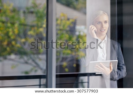 A young businesswoman seen talking on the phone through her office window, while holding touchpad - stock photo