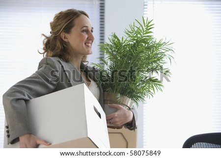 A young businesswoman smiles as she carries her office belongings in her hands.  Horizontal shot. - stock photo