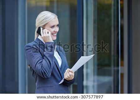 A young businesswoman talking on her cellphone outside - stock photo