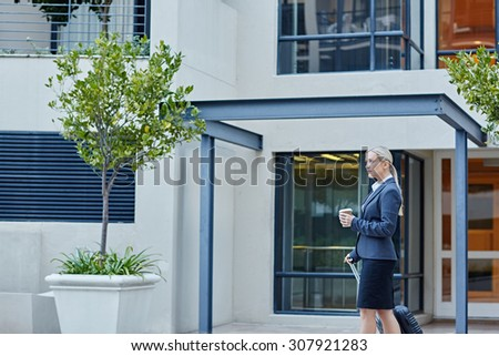 A young businesswoman walking with travel luggage - stock photo