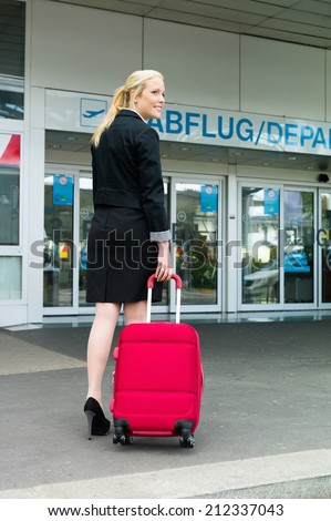 a young businesswoman with suitcase in an airport. - stock photo