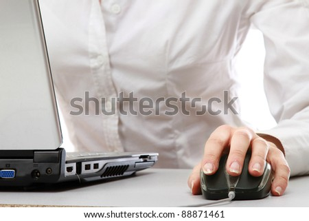 A young businesswoman working on a laptop, focus on her hands - stock photo