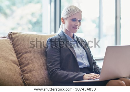 A young businesswoman working on her laptop while sitting on a sofa - stock photo