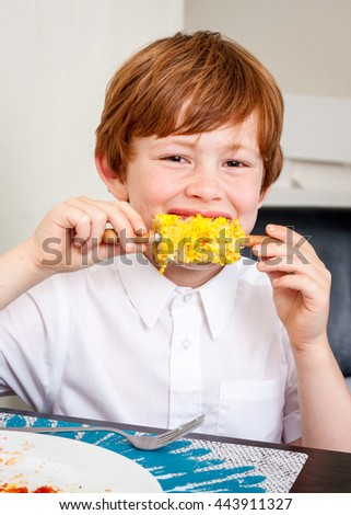A young caucasian boy looking at the camera and smiling whilst eating corn on the cob - stock photo
