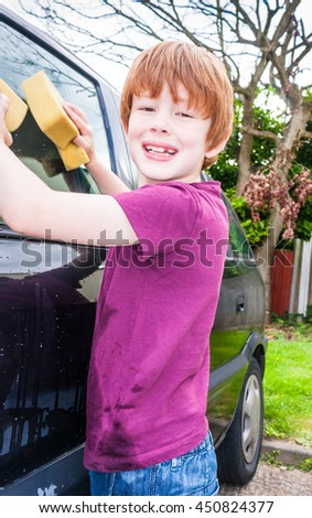 A young caucasian boy looking straight at the camera and smiling whilst washing a car - stock photo