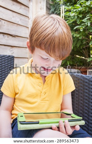 A young caucasian boy playing with a tablet in the garden - stock photo