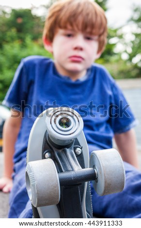 A young caucasian boy sat down, looking at the camera, in the background with the roller-skates he is wearing in focus in the foreground - stock photo
