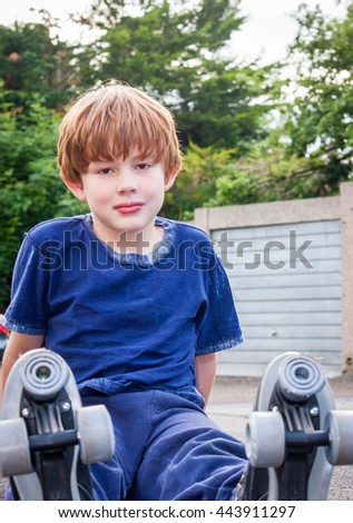 A young caucasian boy sat down outside wearing a pair of roller-skates - stock photo