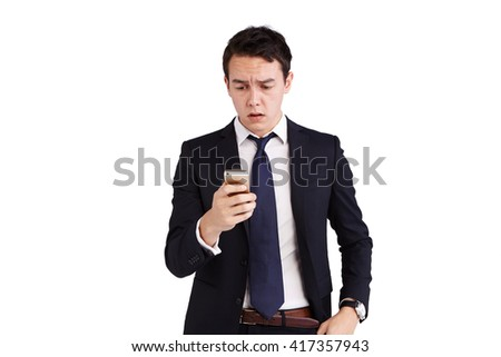 A young Caucasian business man is frowning holding a mobile phone.  - stock photo
