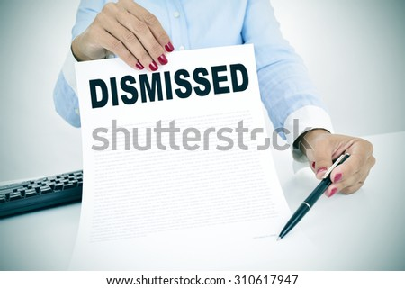 a young caucasian businesswoman sitting at his office desk shows a document with the word dismissed written in it and points with a pen where to sign - stock photo