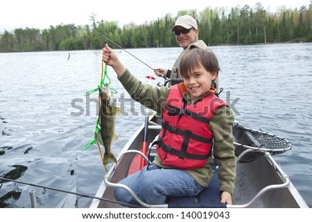 A young caucasian fisherman proudly holds up his first walleye of the day - stock photo