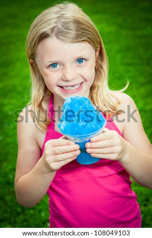 A young Caucasian girl holds a snow cone as she smiles at the camera. - stock photo