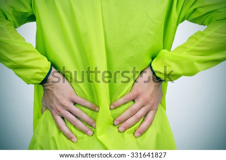 a young caucasian sportsman wearing sport clothes with his hands in his back because of his low back pain - stock photo