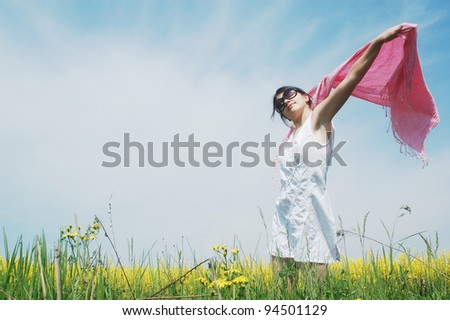 A young caucasian woman enjoying a sunny day on a field of spring flowers. - stock photo
