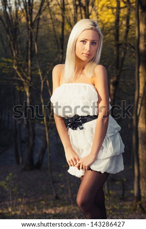 A young caucasian woman posing in a forest. - stock photo