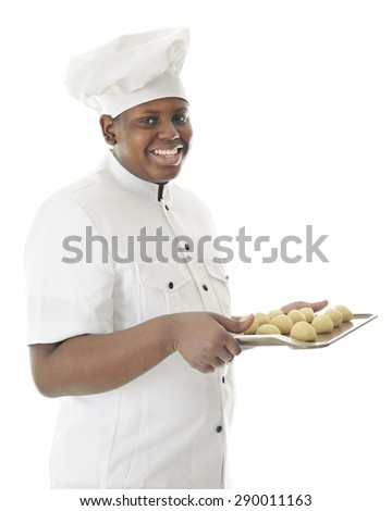 A young chef happily looking at the viewer as he carries a cookie sheet filled with a dozen balls of dough.  On a white background. - stock photo