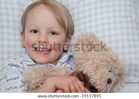 A young child cuddling his teddy at bed time. - stock photo