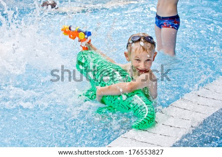 A young child enjoying the water and his water toys. - stock photo