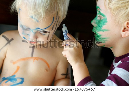 A young child his carefully coloring with a marker all over his baby brother's face and skin - stock photo