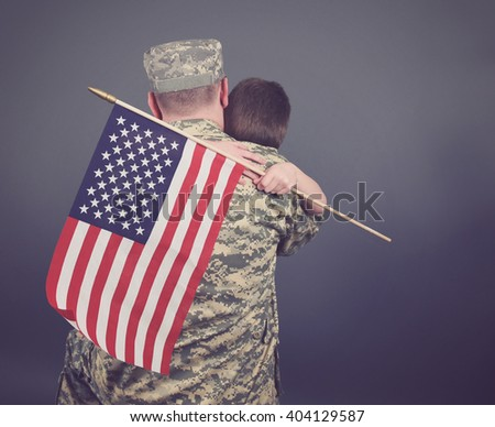 A young child is hugging his army soldier father and holding a usa flag. The child and dad are isolated on a blue background for a patriot or family concept. - stock photo