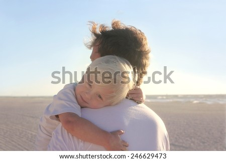 A young child is resting in his father's safe and protective embrace while on a walk on the white sand beach by the ocean at sunset. - stock photo