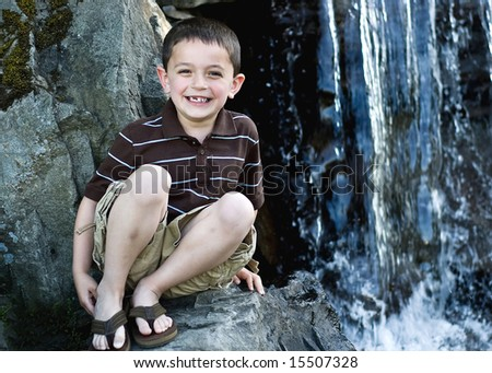 A young child is sitting on a rock next to a waterfall.  He is smiling and looking at the camera.  Horizontally framed shot. - stock photo